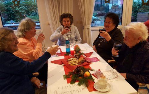 Ein Glas Rotwein gehört für dies Damen zu einer Adventsfeier.