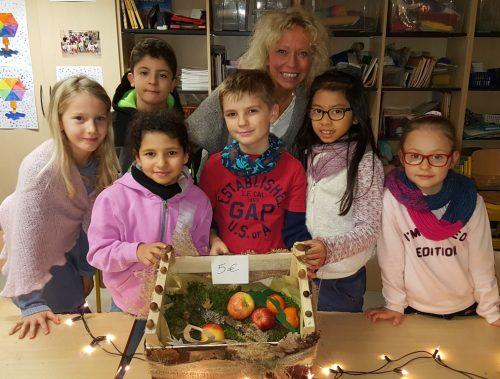 Lehrerin Martina Liesenfeld mit ihren Schülerinnen und Schülern der Klassen 2 b und c mit ihren bunten Obstkisten.