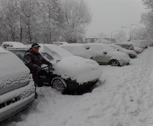 Hermann Kreuzig muss sein Auto am Neujahrsmorgen von einer hohen Schneeschicht befreien. Foto: Krüger